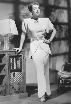 Joan Crawford modeling Change, a two-piece silk dinner dress with gold paillettes designed by Gilbert Adrian
